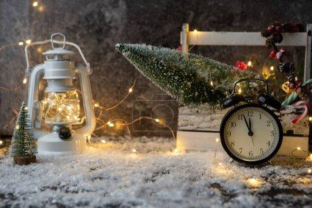 Photo pour Photo de la lanterne, horloge, boîte avec arbre de Noël, brûlant la guirlande sur un tableau noir avec de la neige - image libre de droit
