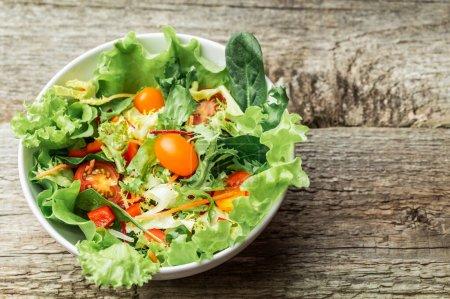 Photo pour Salade de roquette fraîche de légumes - tomates, carottes, poivrons et salade mesclun -, mesclun, mâche - sur fond en bois. - image libre de droit