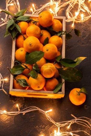 Photo pour Photo de tangerines dans une boîte en bois sur une table noire avec guirlande - image libre de droit