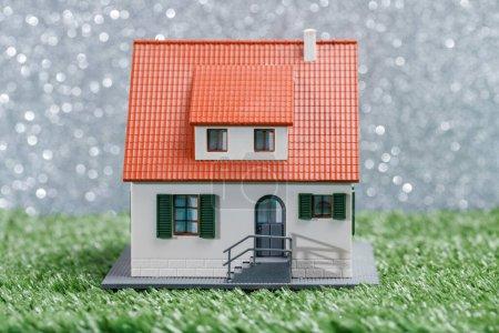Photo pour Image de maison de jouet sur herbe verte à fond gris avec des taches - image libre de droit