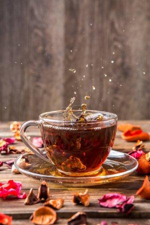 Photo pour Tasse de thé noir sur table avec pétales de fleurs - image libre de droit