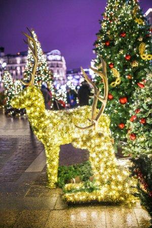 Photo pour Photo du Nouvel An branches décorées de sapins, cerf jouet sur fond flou de lumières allumées - image libre de droit