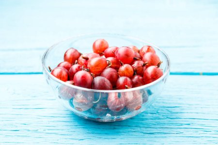 Photo for Photo of red gooseberry on wooden table - Royalty Free Image