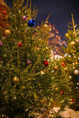 Photo pour Photo d'un arbre de Noël arborant des balles dorées, bleues et rouges sur fond floue et une guirlande en feu - image libre de droit