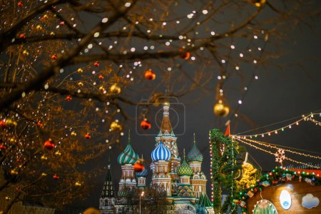 Photo for Image of tree with golden and red balls on background of cathedral in evening - Royalty Free Image