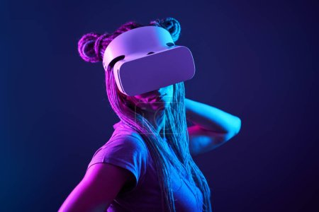 Photo for Woman is using virtual reality headset. Neon light studio portrait. Concept of virtual reality, simulation, gaming and future technology. - Royalty Free Image