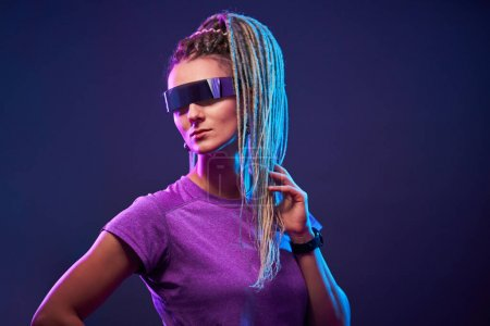 Photo for Young woman with pigtails in sunglasses looking at camera in neon light at disco - Royalty Free Image