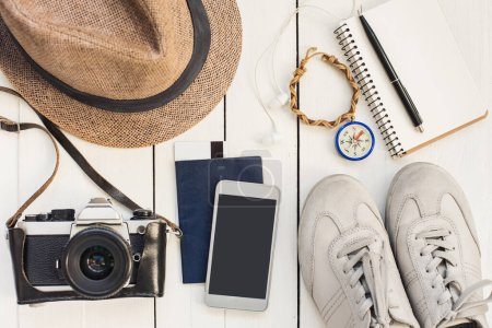 Photo for Accessories for travel. Different objects on wooden background. Passport, photo camera, smart phone, shoes, sunglasses and ebook reader . Top view. Tourism, holidays and tourism concept - Royalty Free Image