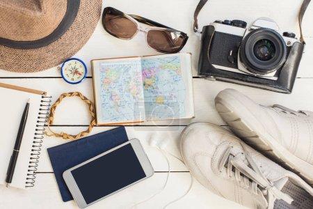 Photo pour Accessoires de voyage. Différents objets sur fond en bois. Passeport, appareil photo, téléphone intelligent, chaussures, lunettes de soleil et lecteur ebook. Vue de dessus. Tourisme, vacances et concept de tourisme - image libre de droit