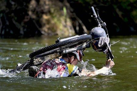 Radler, Abenteurer auf Tour, watet durch den Fluss und Wasser reicht ihm bis zum Kopf, spritzt ihm ins Gesicht und fließt in seinen Rucksack. Fahrrad trägt über Kopf.