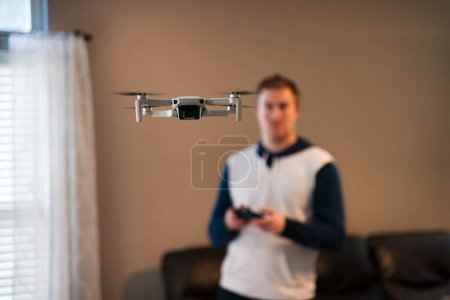Photo for Drone flying indoors with pilot visible in background. Amateur drone flight. User wearing sweatshirt flying drone inside of home on cold day. White drone flying inside. - Royalty Free Image