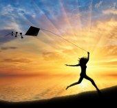 Girl runs with kite near sea