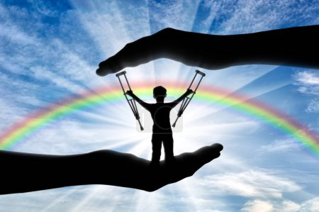 Child disabled person with crutches in hand on background rainbow day