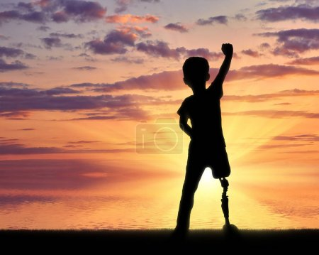 Photo for Children with disabilities concept. Happy disabled boy with a prosthetic leg standing at the sea at sunset - Royalty Free Image