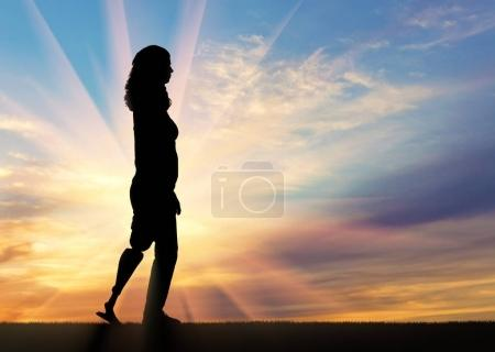 Photo for A silhouette of a woman with a prosthetic leg going up on the slope. The concept of rehabilitation of people with prosthetic legs - Royalty Free Image