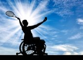 Silhouette of disabled person in a wheelchair playing tennis