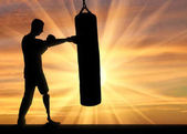 Silhouette of a disabled man with a leg prosthesis, training with a punching bag