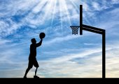 Silhouette of a disabled man with a leg prosthesis intends to throw the ball into the basket