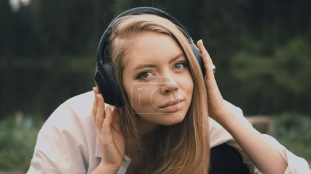 Photo for Beautiful young blonde woman with natural appearance listening to music on black headphones. - Royalty Free Image