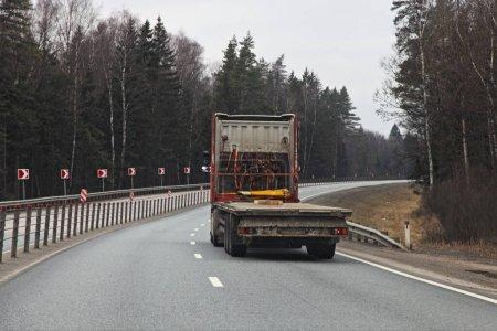 Photo pour Semi-camion avec un chalut semi-remorque vide à châssis bas sur la route goudronnée de banlieue le jour du printemps, vue de l'arrière Logistique, transport, industrie du camionnage - image libre de droit