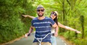 Happy couple riding bicycle in forest