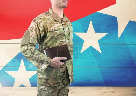 soldier holding a book in front of american flag