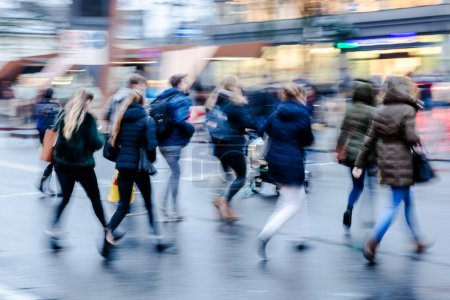 Photo for Picture in motion blur of a wintry street scene in the city with people crossing a street - Royalty Free Image