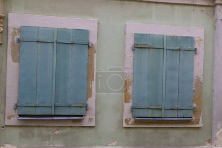Photo pour Deux fenêtres avec volets en bois fermés sur la façade d'une ancienne maison colorée, gros plan. Architecture européenne médiévale. France, Alsace - image libre de droit