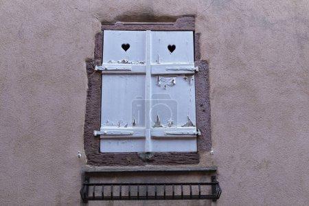 Photo pour Fenêtre avec volets fermés en bois blanc fissurés sur la façade de l'ancienne maison colorée, gros plan. Architecture médiévale européenne. France, Alsace - image libre de droit