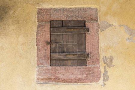 Photo pour Petite porte antique en bois avec un verrou en fer rouillé sur un mur coloré d'une maison. Architecture européenne médiévale. France, Alsace - image libre de droit