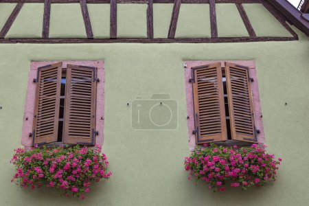 Photo pour Two windows with closed wooden shutters, decorated flowers,  on the facade  of  ancient  colorful house, close-up. Medieval European architecture. France, Alsace - image libre de droit