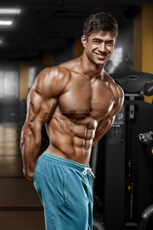 Sexy muscular man in gym, shaped abdominal. Strong male naked torso abs, working out