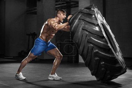 Photo pour Homme musclé dans gym renversant des pneus, abs solide torse nu masculin - image libre de droit
