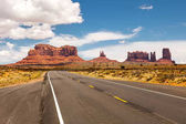 Road passing through Monument Valley, beautiful sunny day with blue sky in summer, Utah, USA