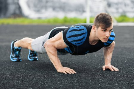 Photo for Fitness man doing push-ups in the stadium, cross training workout. Active male training outdoors - Royalty Free Image