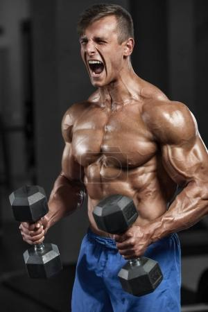 Photo for Muscular man working out in gym doing exercises with dumbbells, strong male naked torso abs - Royalty Free Image