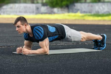 Photo pour Homme de fitness actif faisant de l'exercice de planche dans le stade, entraînement musculaire masculin, extérieur - image libre de droit