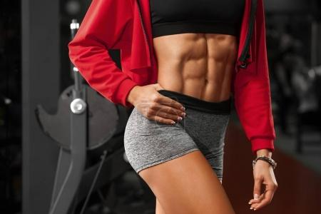Photo for Fitness woman showing abs and flat belly in gym. Beautiful athletic girl, shaped abdominal, slim waist - Royalty Free Image