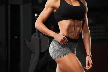 Photo pour Fitness femme sexy montrant abdos et ventre plat dans la salle de gym. Belle fille sportive, en forme d'abdomen, taille fine - image libre de droit