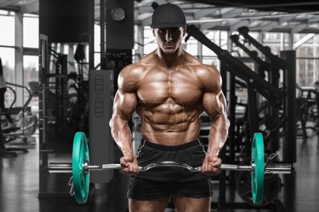 Photo for Muscular man working out in gym doing exercises with barbell at biceps, strong male naked torso abs - Royalty Free Image