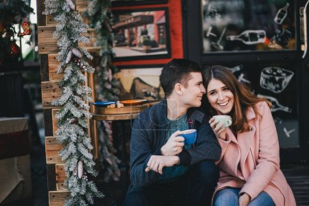 Happy couple in warm clothes drinking coffee on a Christmas market