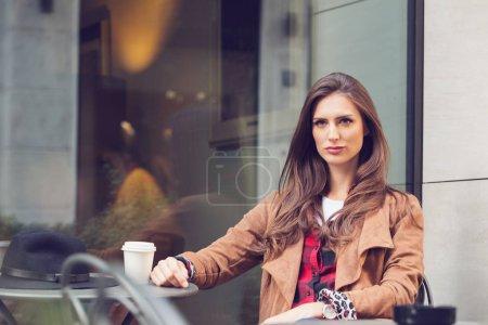 Photo pour Jeune femme assise dans un café à l'extérieur - image libre de droit