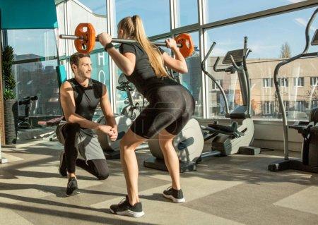 Photo pour Entraînement de femme avec entraîneur de fitness personnel dans la salle de gym moderne avec équipement - image libre de droit