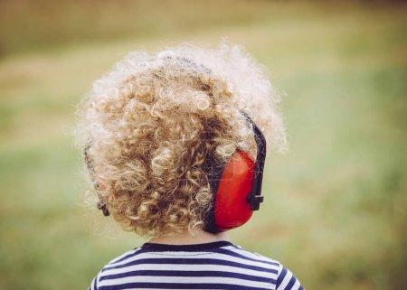 Photo pour Jeune enfant portant un casque anti-bruit lors d'un concert en plein air, empêchant la perte auditive dès le jeune âge concept . - image libre de droit