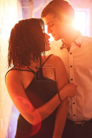 Young people hugging in the apartment in the evening in the rays of the sunset