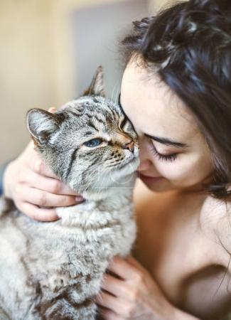 Happy beautiful young woman in the morning in bed with a cat