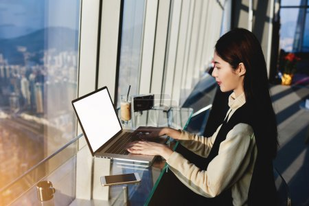 Young asian woman working with modern computer in cozy coffee shop with city space view