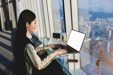 young asian woman work on laptop computer with blank screen