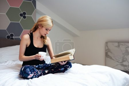 Charming hipster girl with cup of tea in hand is reading interesting book, while is relaxing in her house inside