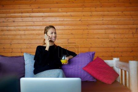 Smiling woman freelancer is talking via smart phone during break between work in internet via portable net-book.